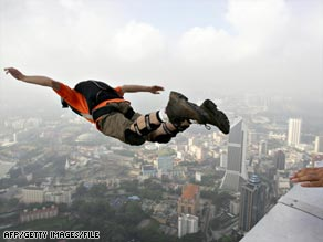 Open to risk -- a skydiver leaps off a building in Malaysia
