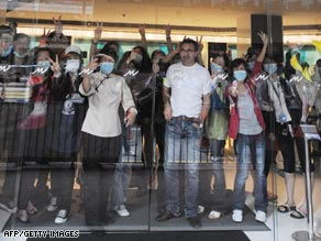 Quarantined guests at Hong Kong's Metropark hotel wave to world press.