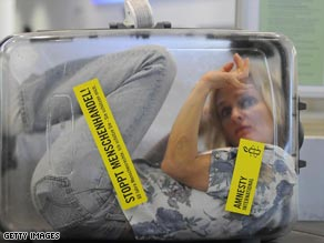"A protestor locked in a suitcase reading ""Stop Human Trafficking"" in Germany last year."