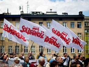 Shipyard workers hold Solidarity trade union flags on the anniversary of free elections in Poland.