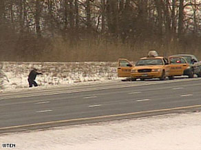 A law enforcement officer approaches the gunman Saturday along Interstate 90 in New York.