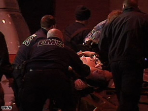 One of the injured officers is taken out of an ambulance and rushed into the University of Louisville Hospital.