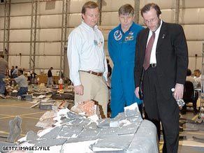 Courtney Stadd, right, is seen examing debris from the Space Shuttle Columbia break-up in 2003.