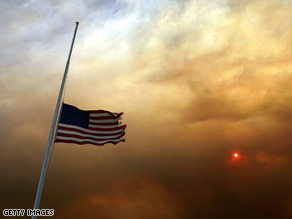 Smoke rises over a flag flying at half-staff for fallen firefighters October 27, 2006, in Banning, California.