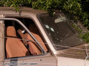 Bullet holes pocked the windshield of the crashed SUV, and blood stained he passenger seat.