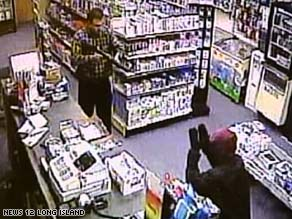 Surveillance video shows storekeeper Mohammad Sohail holding a robber at bay with a shotgun.