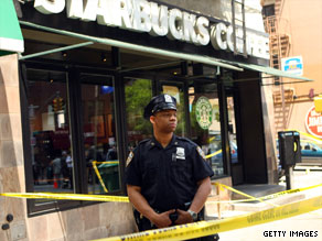 An NYPD officer stands guard outside a Starbucks where a bomb went off on Memorial Day.