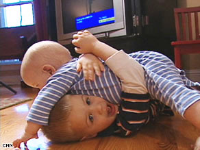 Hank Austin, bottom, and his brother, Jake, play together on the floor. What about germs?