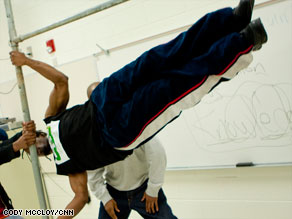 Metaphysics does inverted pull-ups as Bartendaz founder Hassan Yasin keeps the bar steady.