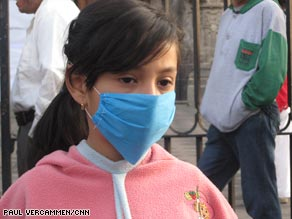 A girl in Mexico City wears a mask outside the Metropolitan Cathedral on Sunday.