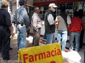 Concerned residents line up outside a pharmacy Monday in Mexico City, Mexico.