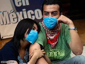 A young couple in Mexico City wear surgical masks in an attempt to avoid contamination from the virus.