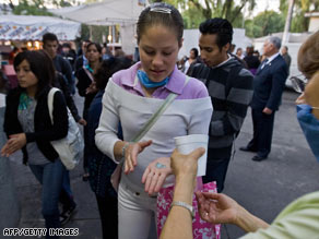 A student uses disinfectant as she arrives Thursday at the National Technical Institute in Mexico City.