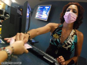 A movie theater attendent in Guadalajara, Mexico takes precautions at work.