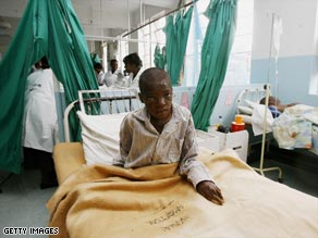 A Zimbabwean cholera patient sits in his bed  at a hospital in Harare. The rainy season could threaten more lives.