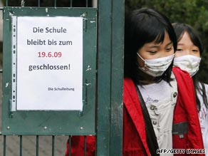 Children walk through the front gate of a Japanese school in Germany which has been closed following a swine flu outbreak.