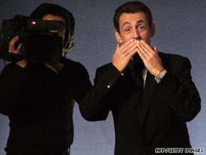 The future of French kissing? French President Nicolas Sarkozy keeps his distance with a kiss and a wave