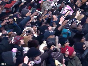 Crowds at the inaugural parade cheer and snap photos of President Obama on Tuesday.