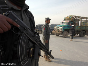 An Afghan policeman stands guard watching traffic at a checkpoint in Kabul, Afghanistan, Thursday.