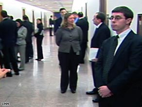 Aides to the senators wait in the hall as Thursday's meeting takes place.