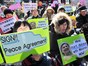 Anti-war activists hold placards during a rally near the U.S. embassy in Seoul on Tuesday.