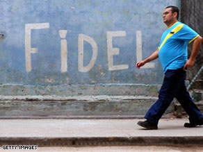 A man passes in front a graffiti reading 'Fidel' in Havana, Cuba.