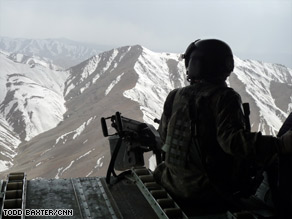 A U.S. soldier flies over Afghanistan aboard a Chinook helicopter in March.
