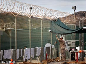 A guard leans on a fence talking to a detainee inside the U.S. Naval Base in Guantanamo Bay, Cuba.