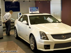 A customer looks at a new car in a GM showroom -- but GM sales are down 30 percent this year.