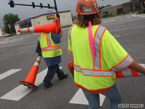 Road construction employees work on a project funded by the federal stimulus in May in Littleton, Colorado.