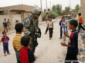 A U.S. soldier plays soccer with children in mid-June in the northern Iraqi city of Mosul.