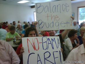 People protest President Obama's health care plan Wednesday at a town hall meeting in Panora, Iowa.
