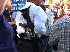A man is shown legally carrying a rifle at a protest against President Obama in Phoenix, Arizona.