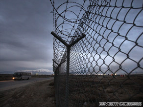 A bus passes a fence topped with razor wire at Bagram Air Base, Afghanistan, earlier this year.