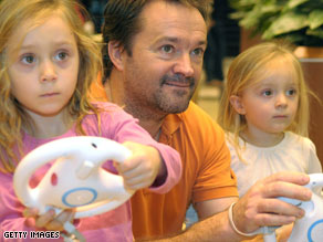Roger Walland and daughters Rachel, 5, and Jennifer, 2, of Plano, Texas, play with Nintendo's popular Wii system.