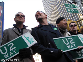 "U2 -- Adam Clayton, Bono, The Edge and Larry Mullen Jr. -- hold signs for ""U2 Way"" Tuesday in New York."