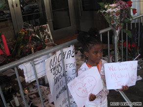 A girl holds up signs in memory of Michael Jackson outside New York's Apollo Theater on Saturday.