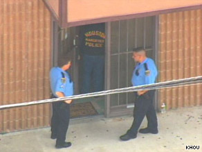 Officers stand outside the Houston, Texas, building where Dr. Conrad Murray has an office.