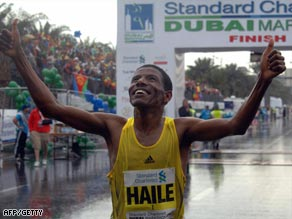 Gebrselassie crosses the finish line in damp and windy conditions in Dubai.