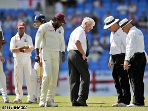 Umpires Rudi Koertzen and Tony Hill inspect the suspect Antigua outfield amid farcical scenes.