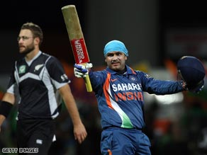 Sehwag celebrates his century with New Zealand skipper Daniel Vettori in the background.