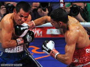 Amir Khan (right) lands another punch on Marco Antonio Barrera on his way to a points victory on Saturday.