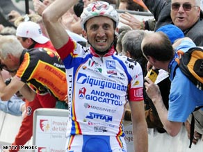 Rebellin becomes crosses the line to become only the fourth rider to win three Fleche-Wallonne titles.