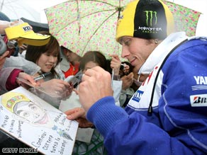 Rossi shelters under an umbrella as he signs autographs at a wet Motegi circuit.