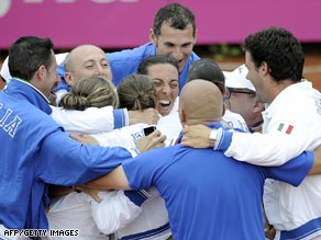 Francesca Schiavone is mobbed by team-mates and coaching staff as Italy reached the Fed Cup final.