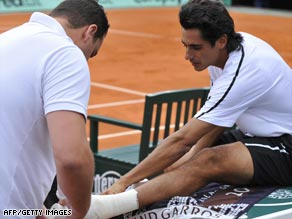Lapentti gets treatment for his ankle injury prior to quitting his first round match against Novak Djokovic.