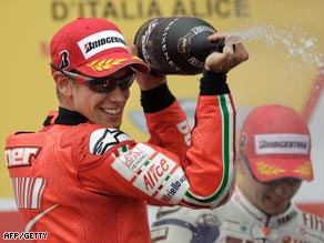 Stoner enjoys his champagne celebration after taking the title lead in Mugello.