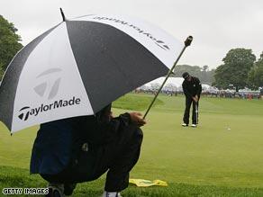 A caddie (L) watches as Japanese golfer Hidemichi Tanaka (R).