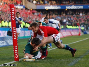 South Africa fly-half Ruan Pienaar is tackled by Lions centers Jamie Roberts, left, and Brian O'Driscoll.