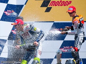 Pedrosa (left) and Rossi share a champagne moment on the Laguna Seca podium.
